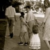 black and white photo of parents walking with kids holding hands