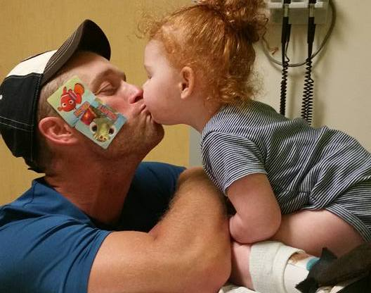 little girl kissing her dad