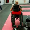 A woman in her wheelchair with something on her lap