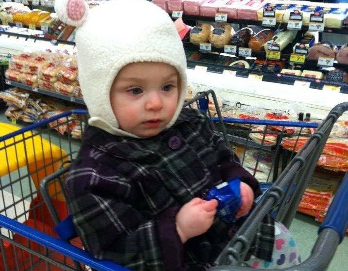 girl wearing bunny hat in shopping cart
