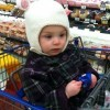 girl wearing bunny hat sitting in a shopping cart