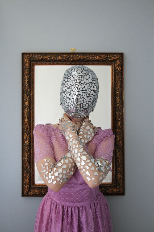 Stone wears a pink dress and a mask made of sharps of glass. She also has glass adorning her arms. She stands in front of an empty picture frame.