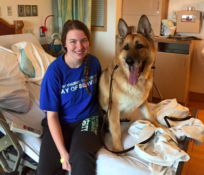 Nora with a therapy dog on a hospital bed