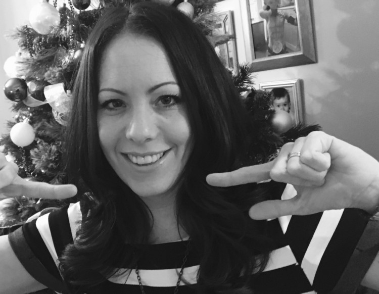 Black and white photo of the author pointing toward herself