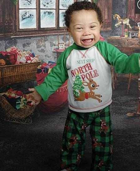 "Jadon wearing a long-sleeved green, red and white shirt that says ""Next Stop North Pole"""