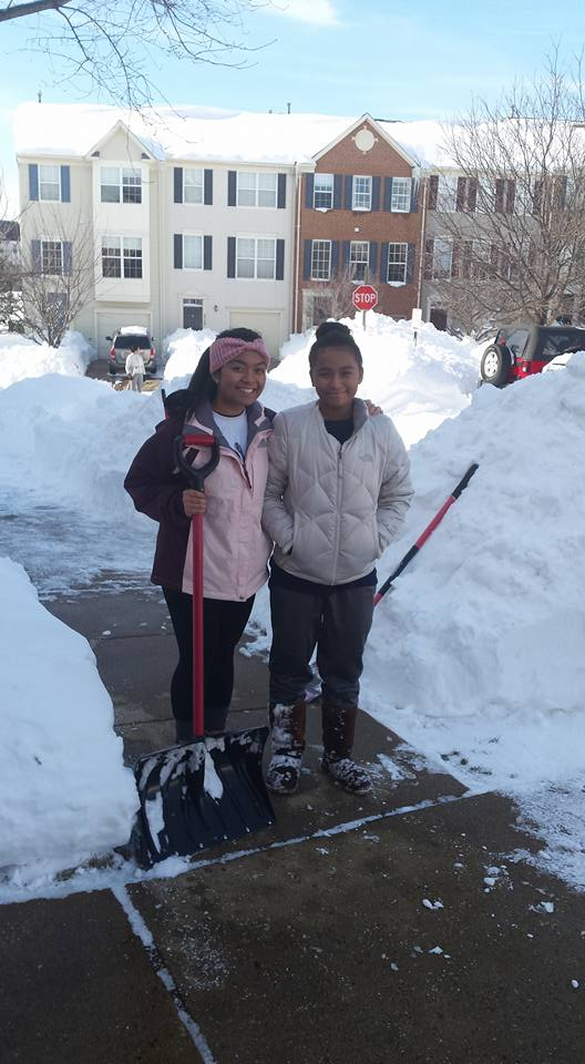 girls helping shovel snow