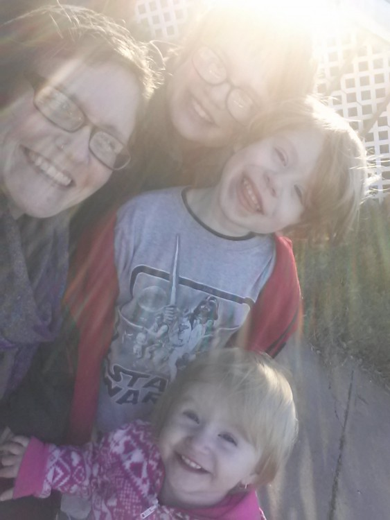 woman smiling with three kids