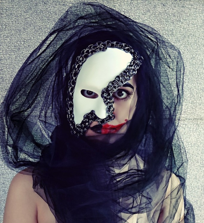 Stone stares into the camera wearing a white mask covering half her fact. The side of her face without a mask shows thickly painted red lipstick.