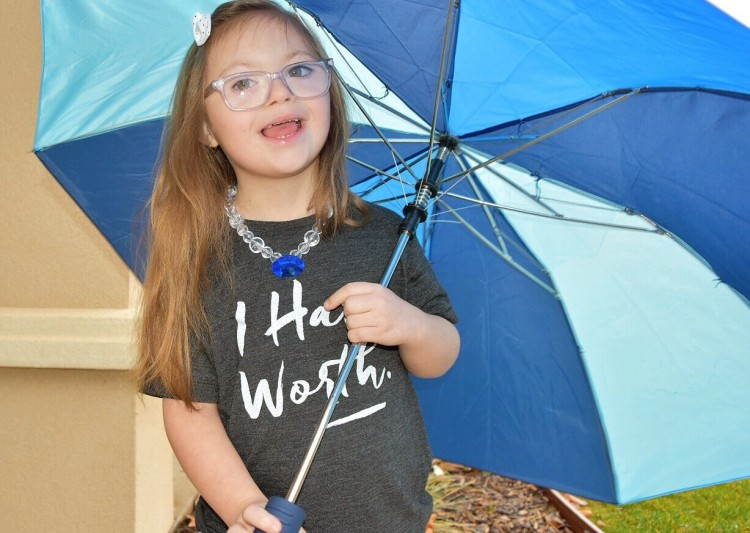 girl holding blue umbrella