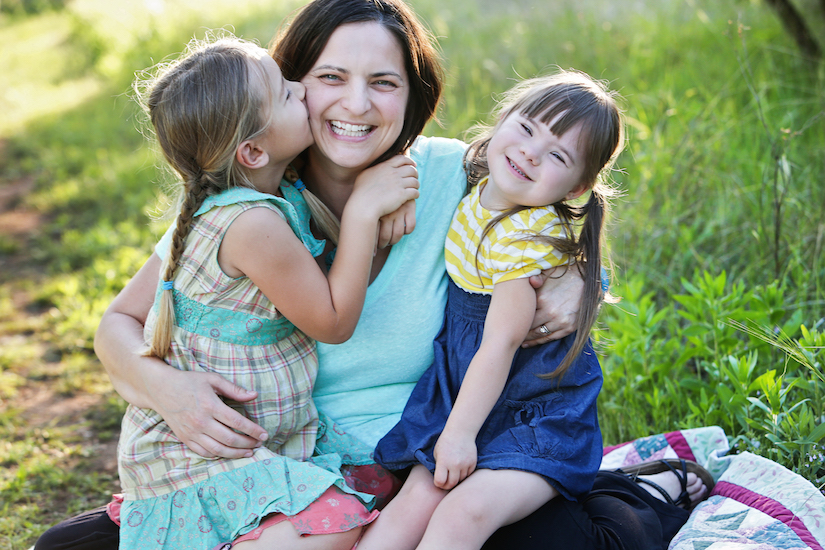 Mom with two daughters sitting outside on the grass