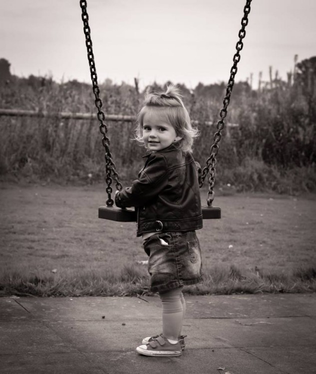 A young girl smiling on a swing.