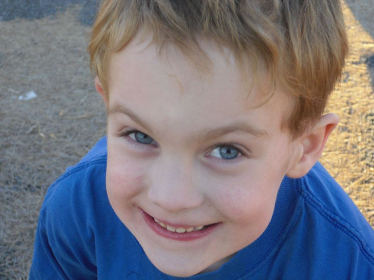 little boy smiling and wearing a blue shirt