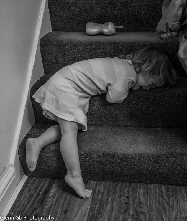 A young girl crying on stairs.