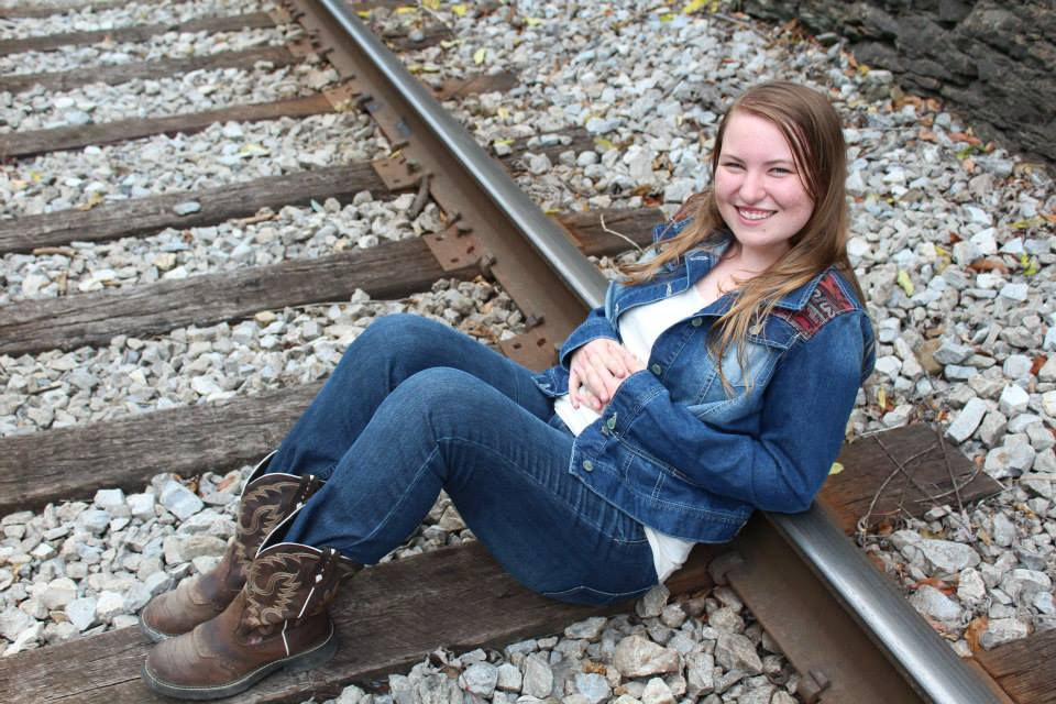 girl sitting on the train tracks, smiling and looking at the camera