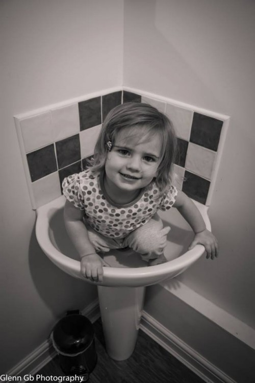 A young girl in a sink.