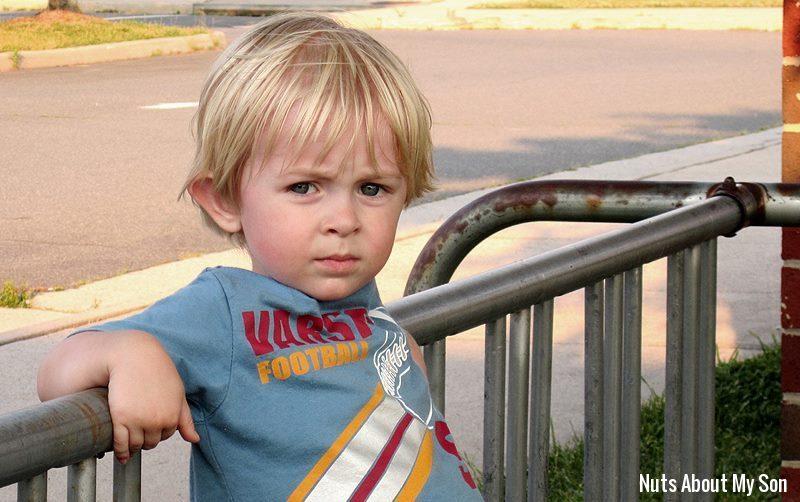 Little boy with blond hair wearing a blue t-shirt