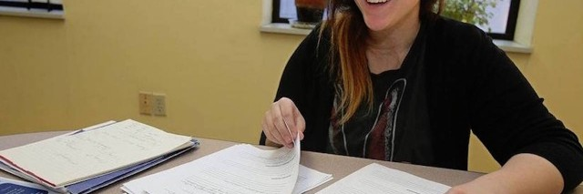 woman laughing and reading over paperwork