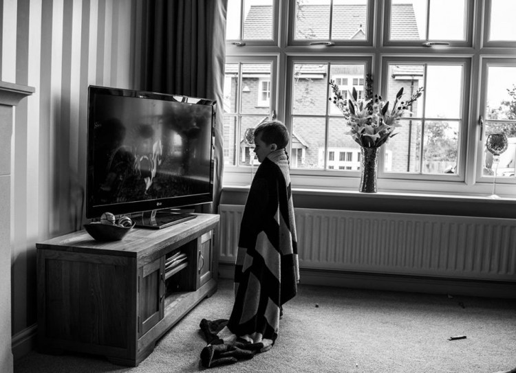 A young boy standing very close to a TV.
