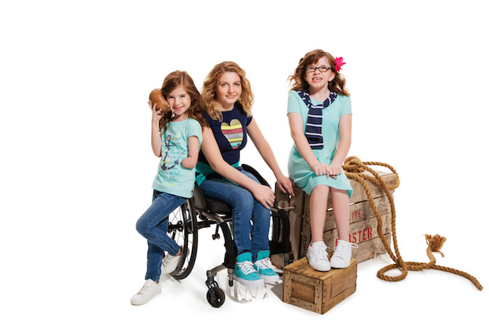 Three children, one in a wheelchair, wearing adaptable clothing.