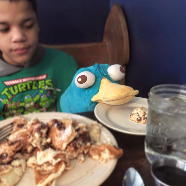boy and stuffed animal sitting at restaurant table