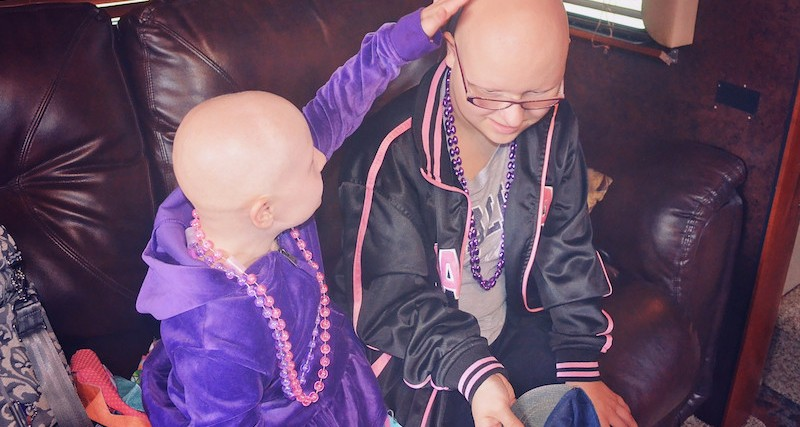 two girls wearing purple beaded necklaces