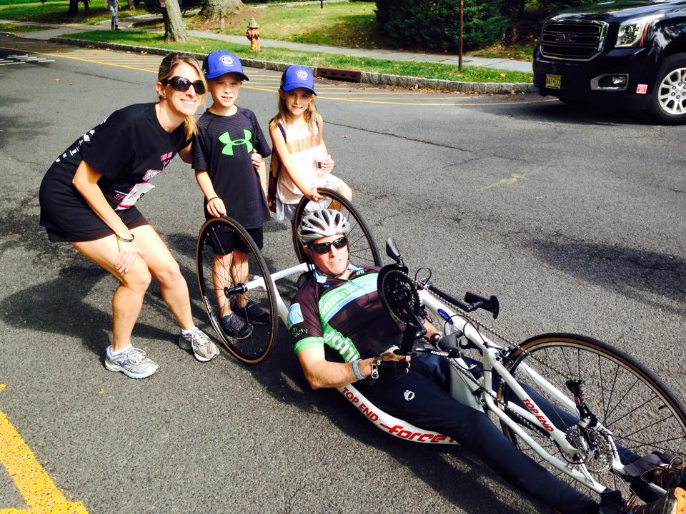Man using a handcycle on the street next to his wife and two kids