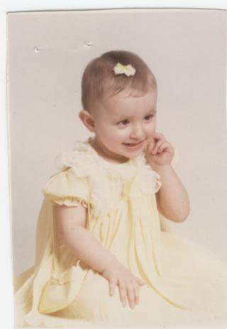 baby girl in a yellow dress with a yellow bow