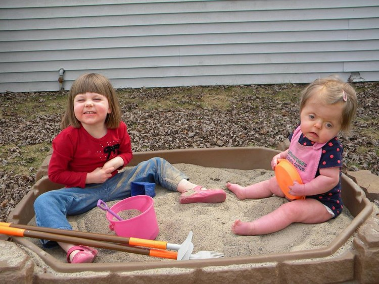 two young girls in sandbox