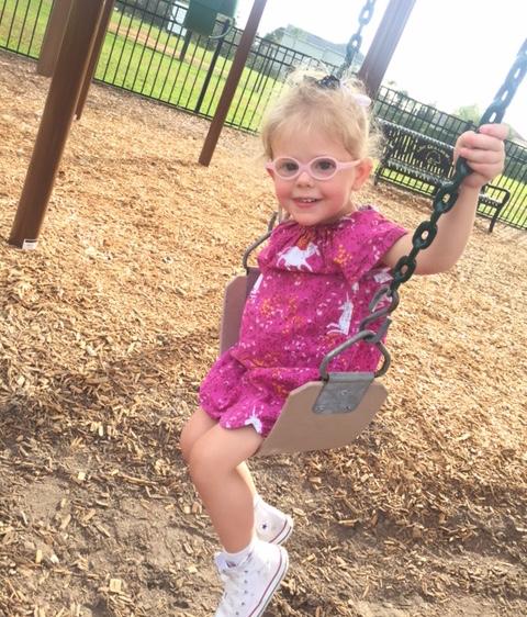 little girl in glasses on swing