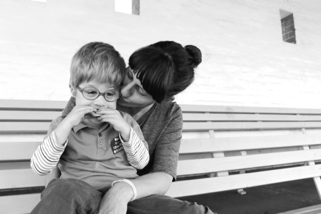 black and white photo of mom kissing her son