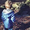 Boy in striped blue and white hoodie standing outdoors