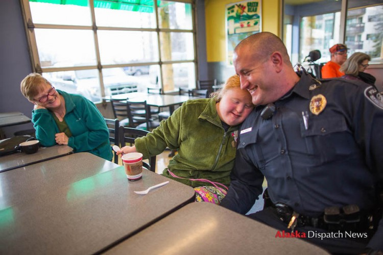 LOREN HOLMES / Alaska Dispatch News Harley Hamilton, a senior at West High living with Down syndrome and autism, gives Anchorage police officer Matt Fraize a side hug at Sagaya City Market on Wednesday, Feb. 24, 2016. Watching at left is DeVon Brentlinger, one of Harley's caregivers.