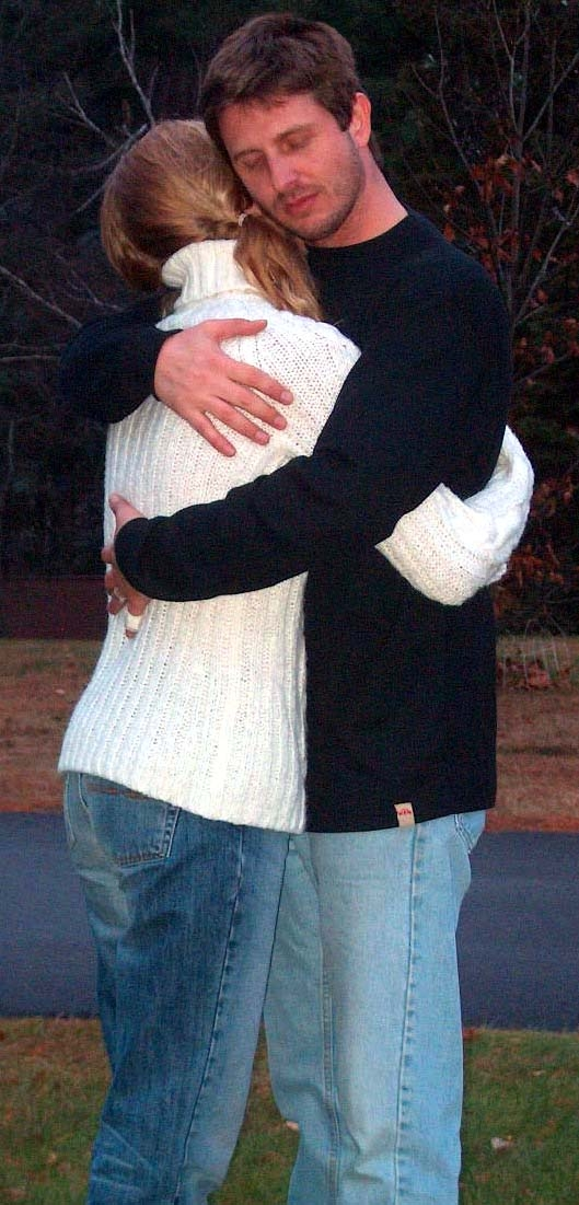 Couple hugging. The woman is wearing a white sweater, and the man is wearing a black sweater. Both of them are in jeans.