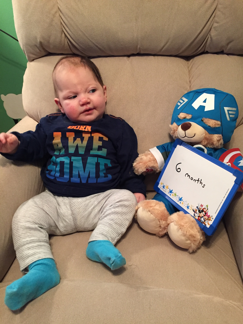 "baby next to teddy bear holding ""6 months"" sign"