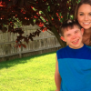 woman standing behind boy in backyard