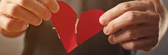hands holding a ripped paper heart