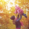 mom holding up baby on walk among trees