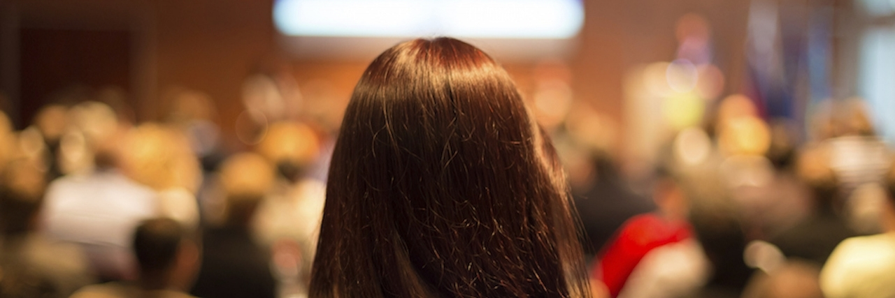 woman standing behind audience at conference hall