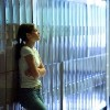 Teenage girl standing by lockers