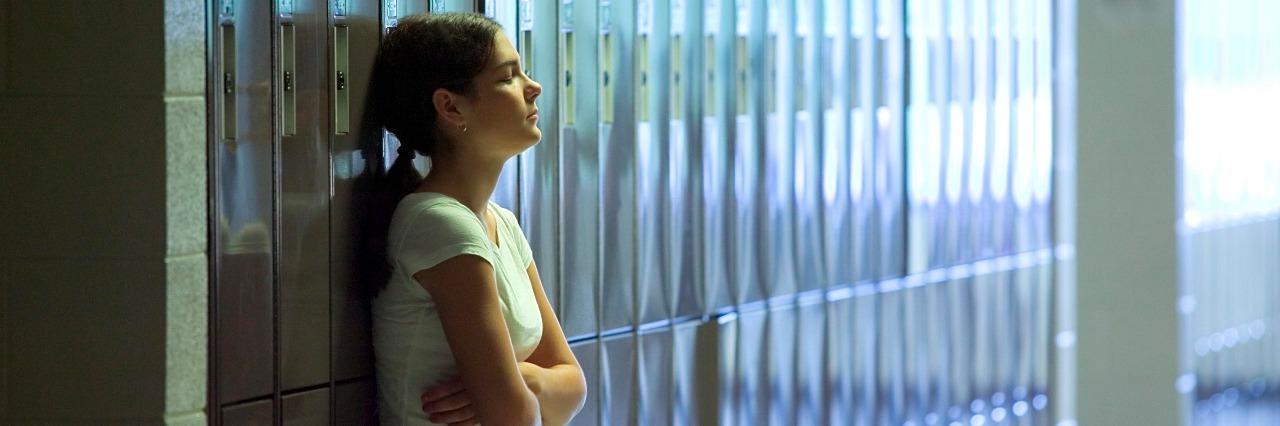 Teenage girl standing by lockers