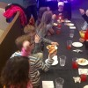 9-year-old boy having a birthday party -- he and his friends are sitting at a table, eating pizza and cheering as he begins to blow out the candle on his cupcake