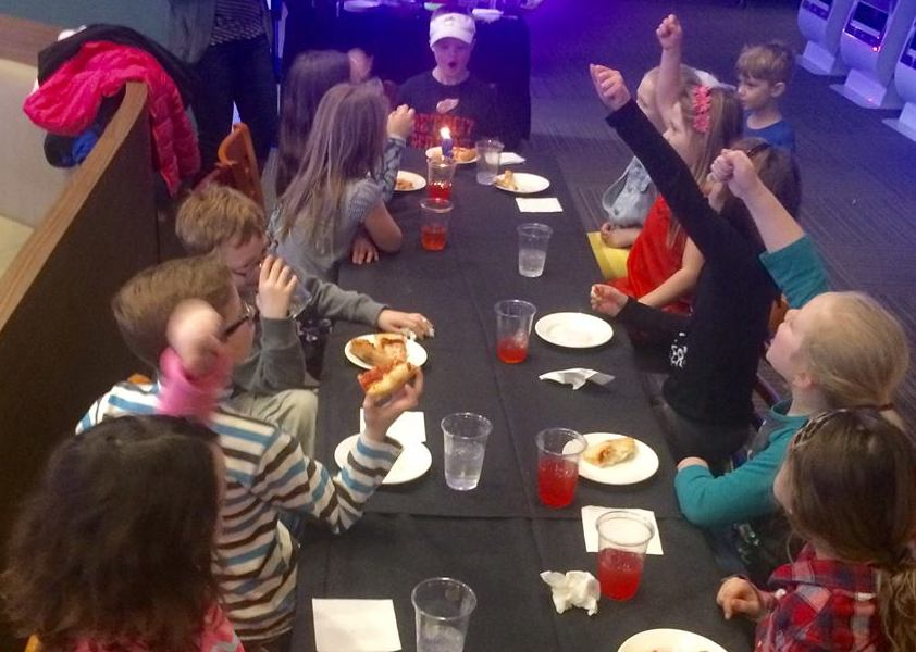 9-year-old boy having a birthday party -- he and his friends are sitting at a table, eating pizza and cheering as he starts to blow out the candle on his cupcake