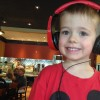 young boy wearing red headphones