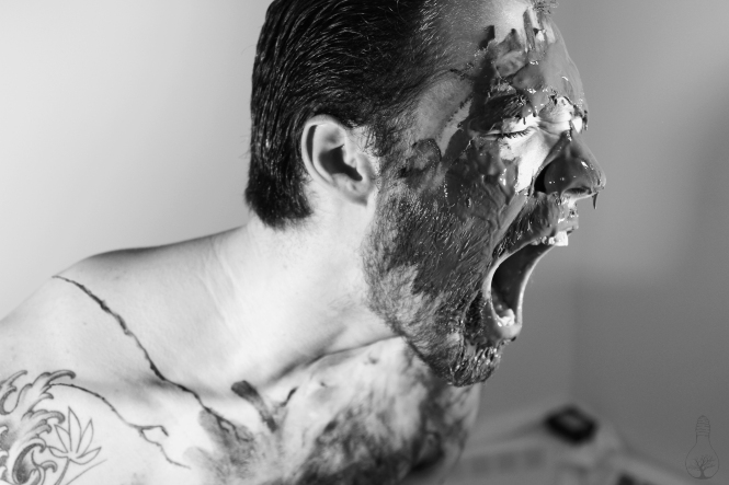 Man screaming, with black all over his face.
