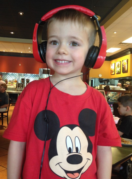boy in mickey t shirt wearing red headphones