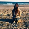 girl sitting on sand looking at ocean