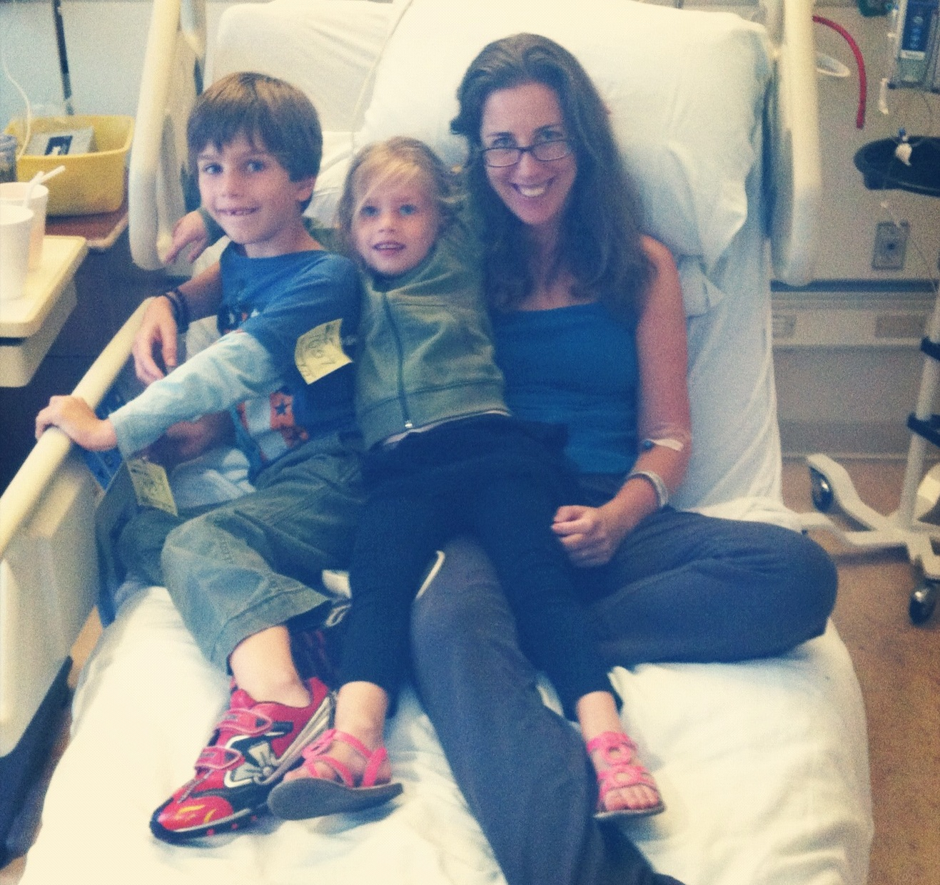 Mom sitting in hospital bed with two kids