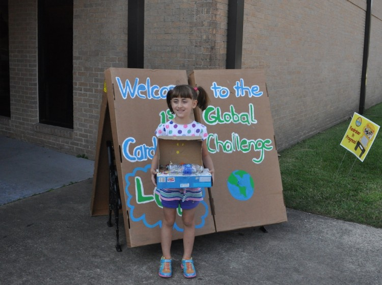 girl standing in front of school holding project
