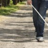 woman walking down path with cane
