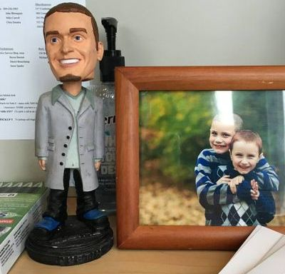 bobblehead of nsync member next to framed photo of two boys